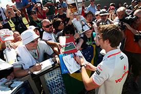 Jenson Button signs autographs for the fans