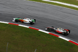 Adrian Sutil leads Lewis Hamilton at Sepang