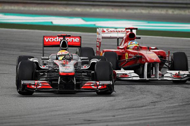 Lewis Hamilton races with Fernando Alonso at Sepang