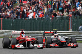 Fernando Alonso is passed by Jenson Button at Spa