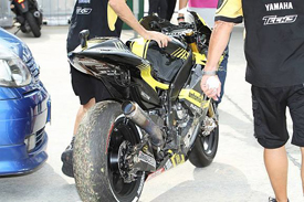 Colin Edwards' Tech 3 Yamaha is brought back to the pits after the crash that killed Marco Simoncelli at Sepang