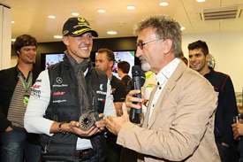 Eddie Jordan presents Michael Schumacher with a souvenir clutch
